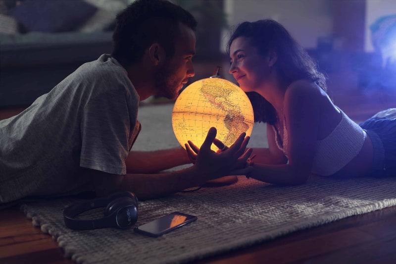 Ein Mann und ein Mädchen liegen auf dem Boden und halten einen Globus in den Händen(1)