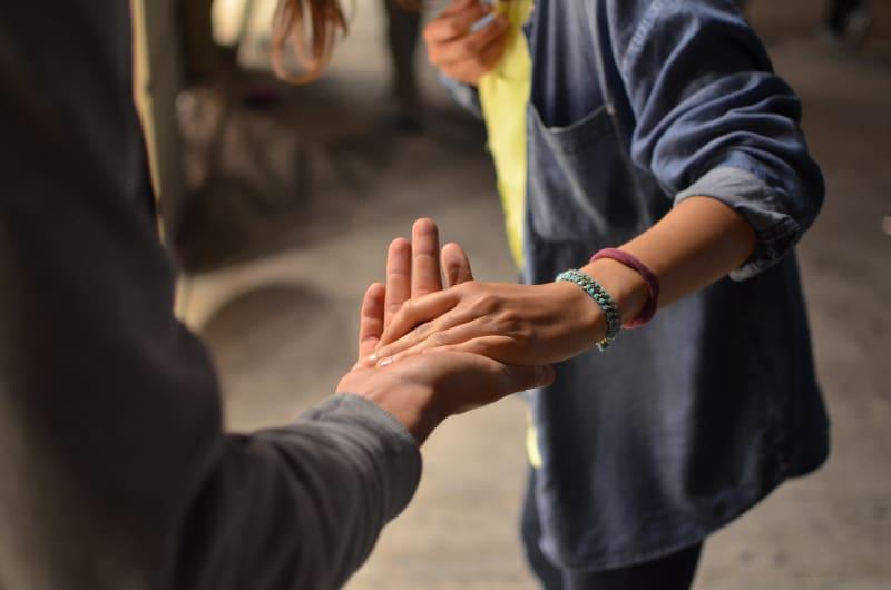 Ein Mann und eine Frau halten sich auf der Straße an den Händen