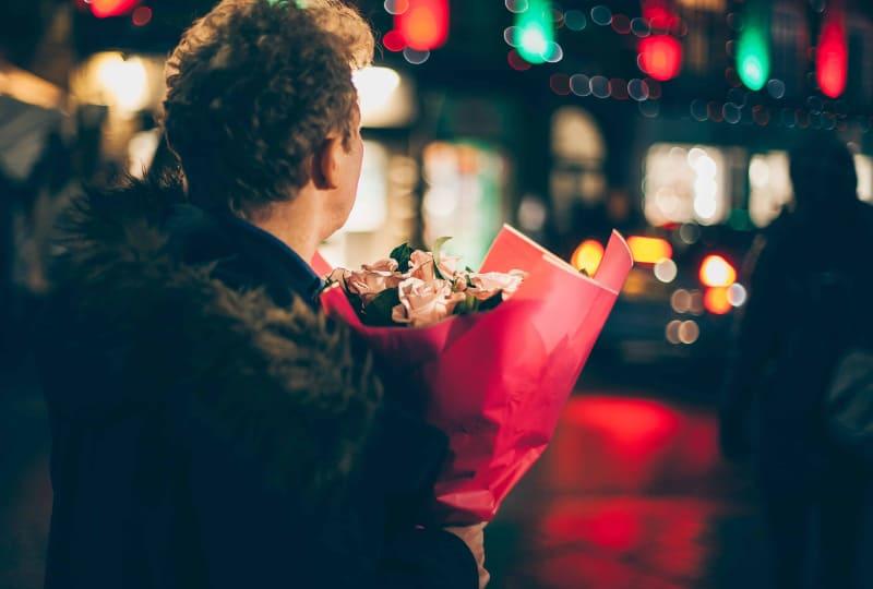 Ein Mann wartet auf ein Mädchen mit einem großen Blumenstrauß(1)