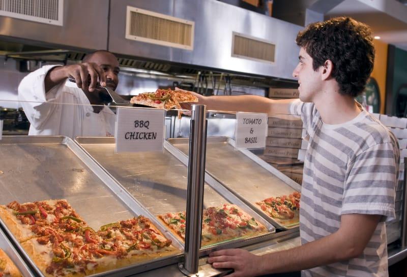 Ein junger Mann kauft ein Stück Pizza in einem Restaurant