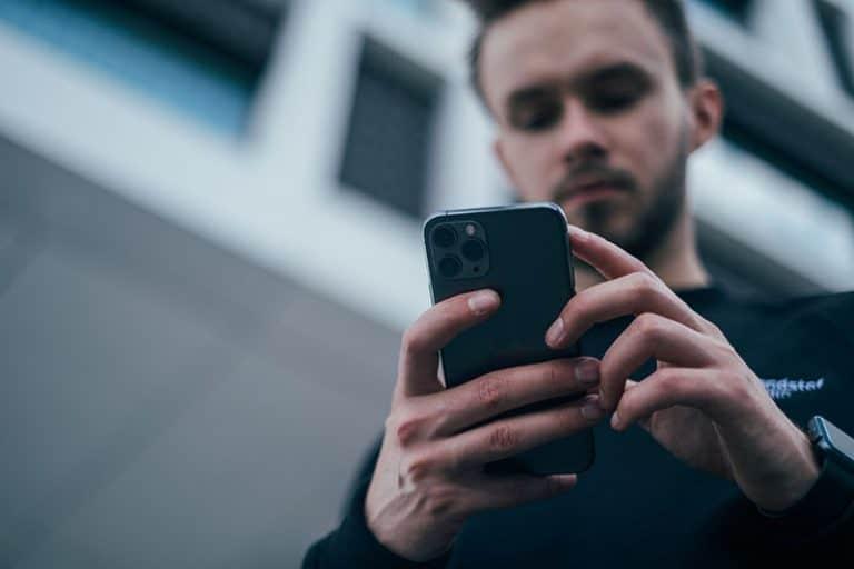 Ein junger Mann schreibt eine Nachricht auf ein Handy