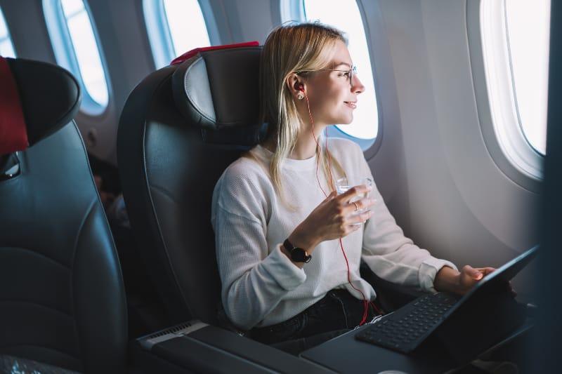 Ein junges Mädchen in einem Flugzeug mit einem Laptop in den Händen schaut aus dem Fenster
