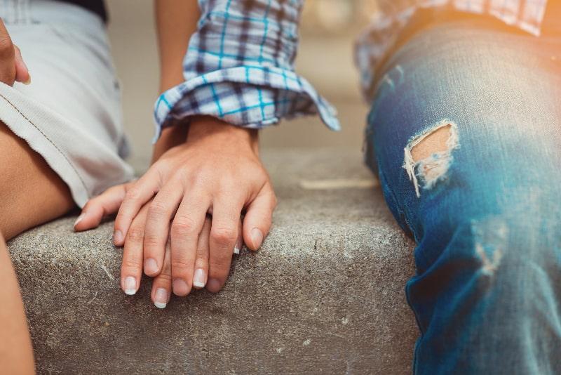 Ein junges verliebtes Paar hält sich an den Händen