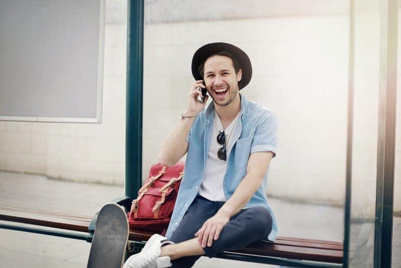 Ein lächelnder Mann mit Schlittschuh und Rucksack spricht auf seinem Handy