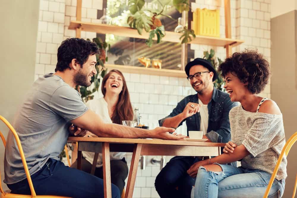 Ein paar Freunde sitzen an einem Tisch und lachen