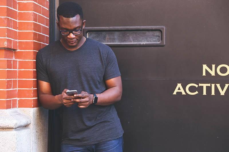 Ein schwarzer Mann mit Brille auf dem Kopf steht auf und schreibt eine SMS