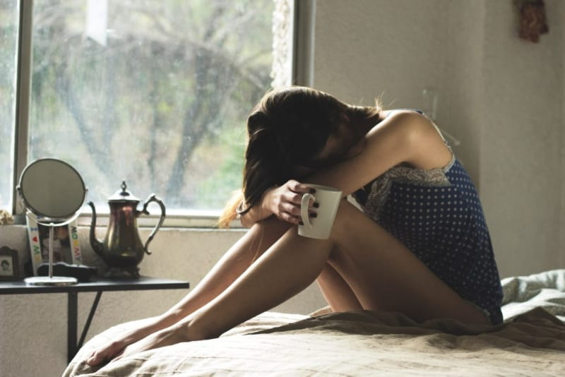 Ein trauriges Mädchen sitzt auf dem Bett(2)