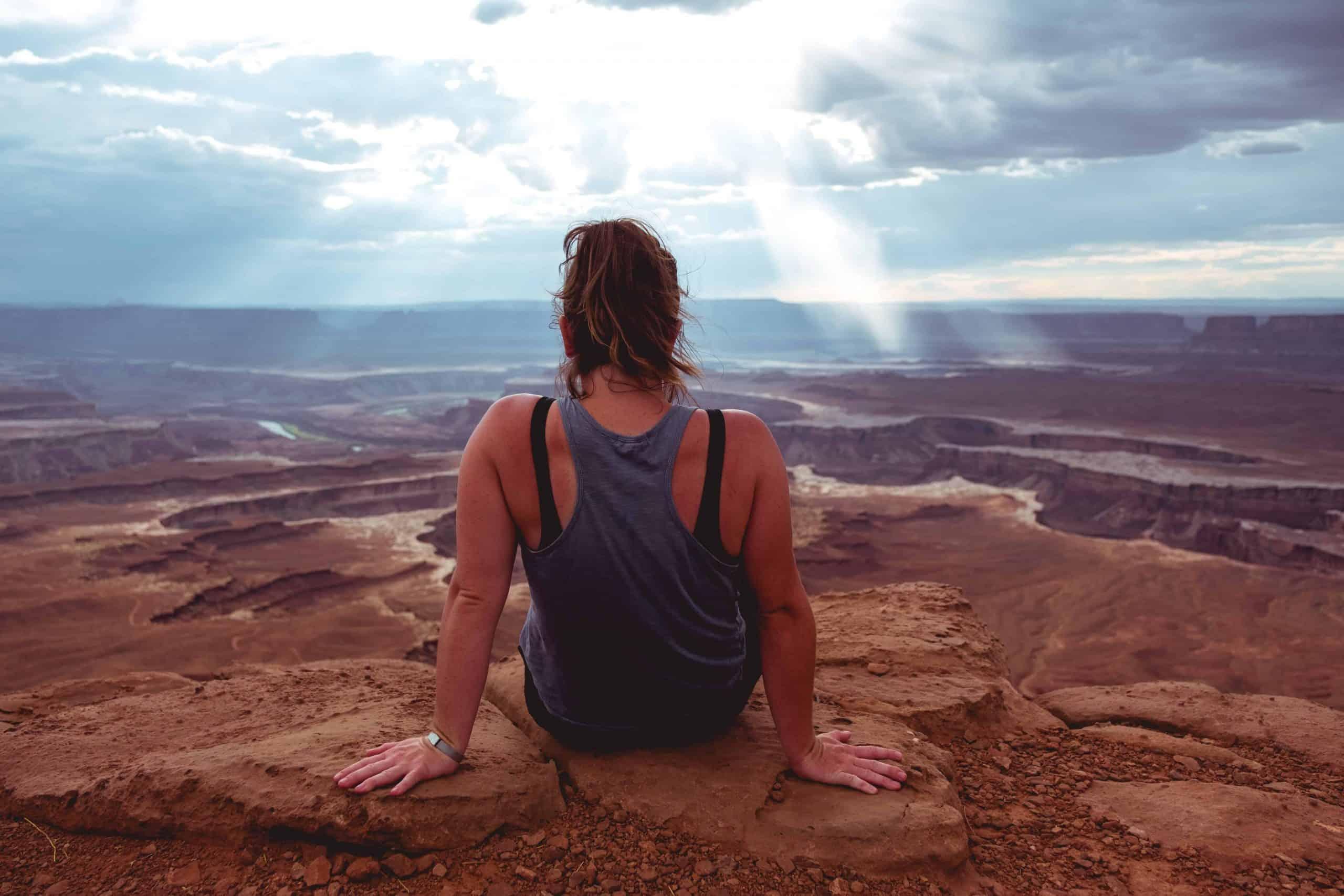 Eine Frau in einem Gürtel sitzt auf einem Felsen