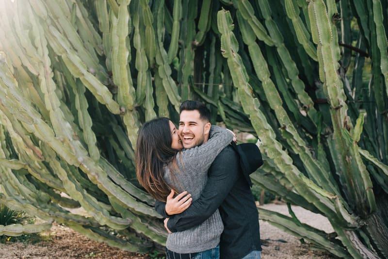 Eine Frau umarmt einen lächelnden Mann neben einem Kaktus