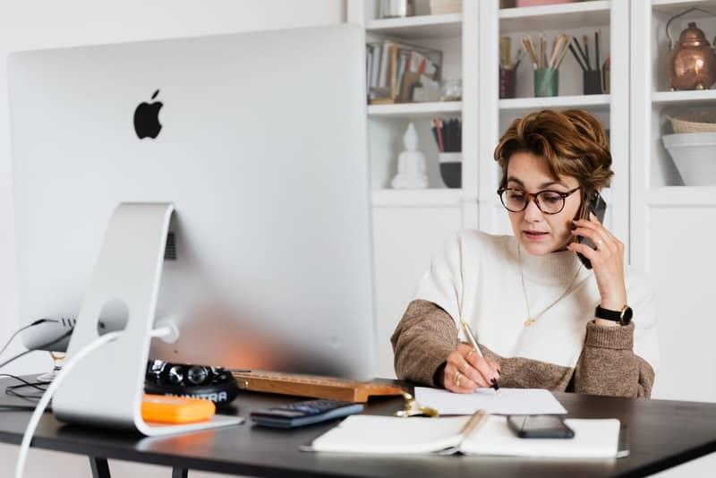 Eine Geschäftsfrau mit Brille sitzt an ihrem Schreibtisch und arbeitet