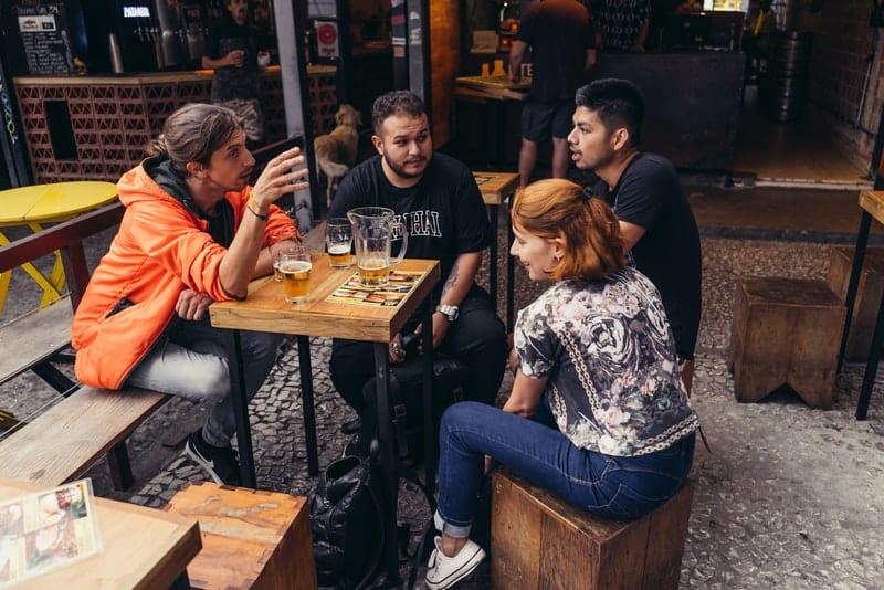Eine Gruppe von Freunden sitzt und redet bei einem Bier