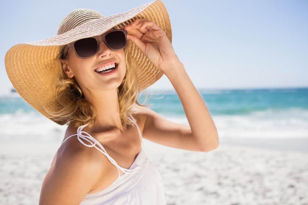 Eine lächelnde Frau mit Sonnenbrille und Hut steht am Strand