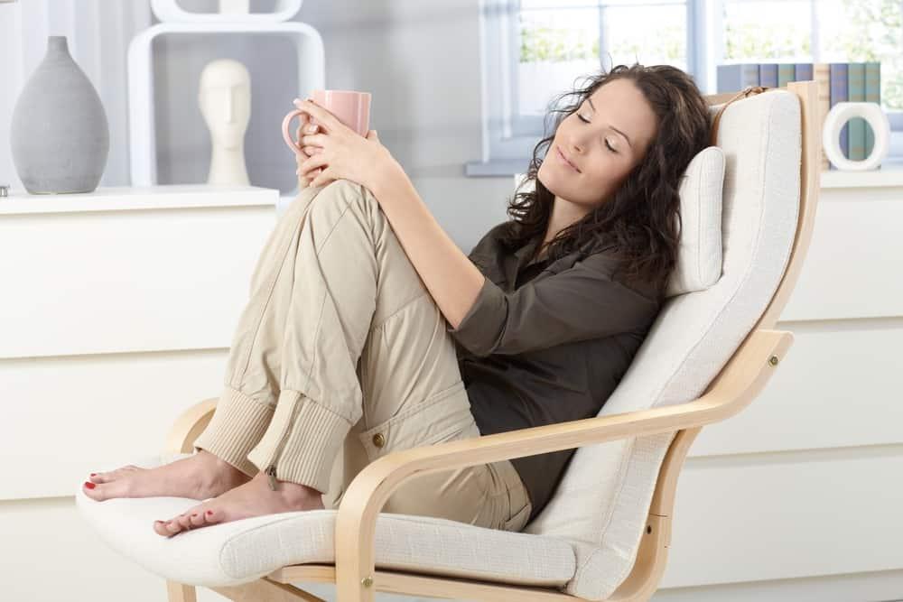 Eine lächelnde Frau ruht mit geschlossenen Augen in einem Sessel