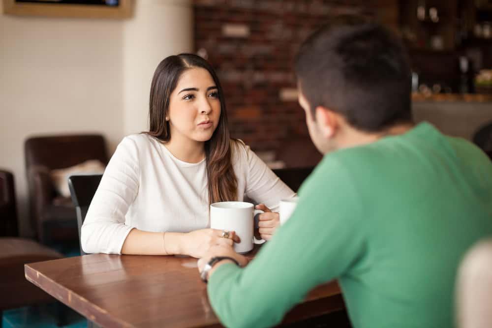 Eine schöne Brünette sitzt in einem Café mit einem Mann in einem grünen T-Shirt und redet