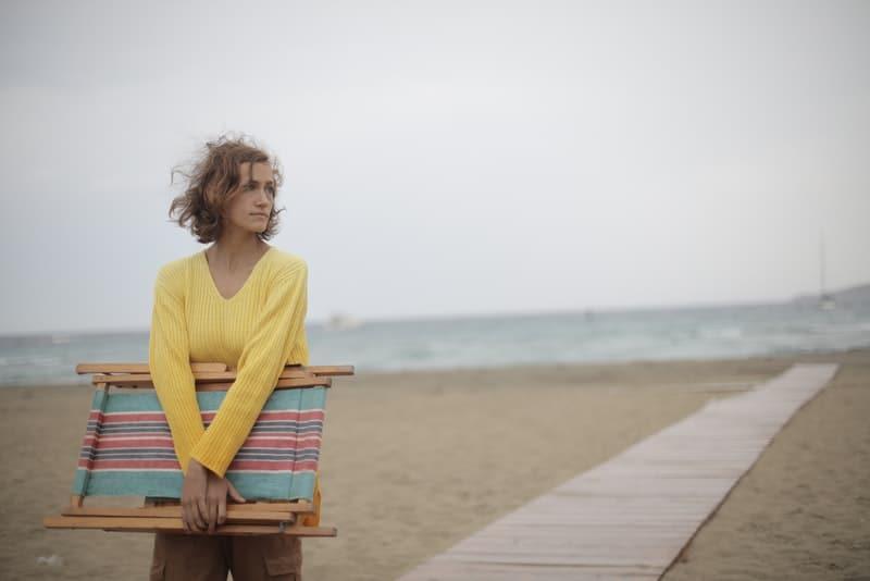 Eine traurige Frau hält eine Liege in den Händen und geht zum Strand