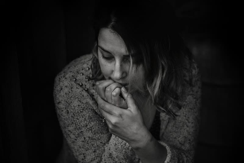 Eine verängstigte Frau sitzt zusammengerollt im Dunkeln