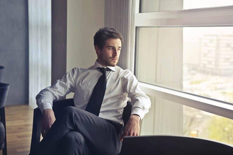 Ein Geschäftsmann im Anzug sitzt am Fenster