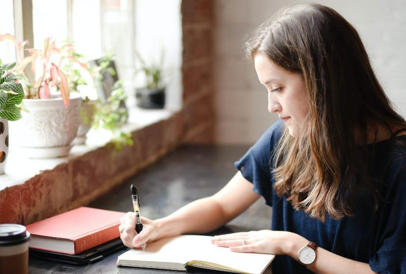 Frau, die vor schwarzem Tisch sitzt, der auf weißem Buch nahe Fenster schreibt