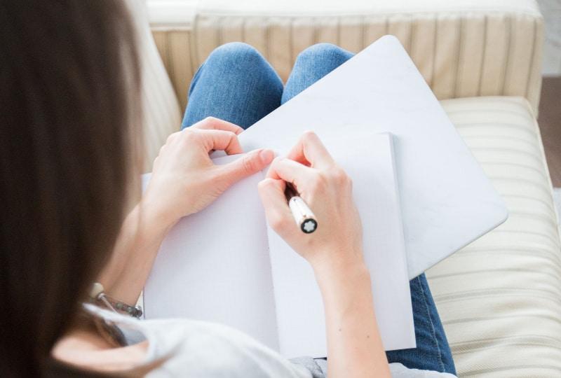 Frau schreibt auf weißem Papier
