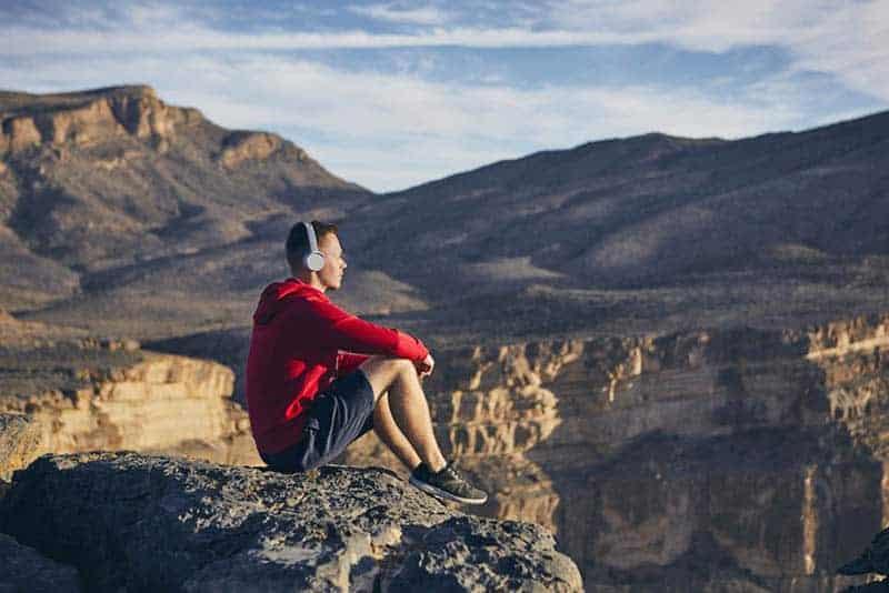 Mann, der Musik hört, während er auf Felsen sitzt