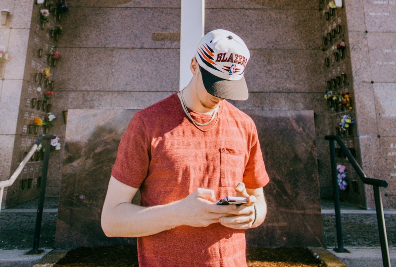 Mann, der Smartphone hält und nahe Kreuzstatue steht