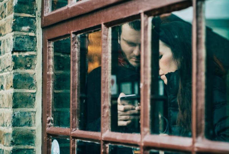 Mann hält Smartphone neben Frau während des Tages