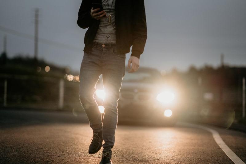 Mann in schwarzer Jacke, der auf Straße geht