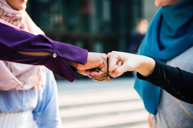 Mann und Frau fisten sich gegenseitig die Hand