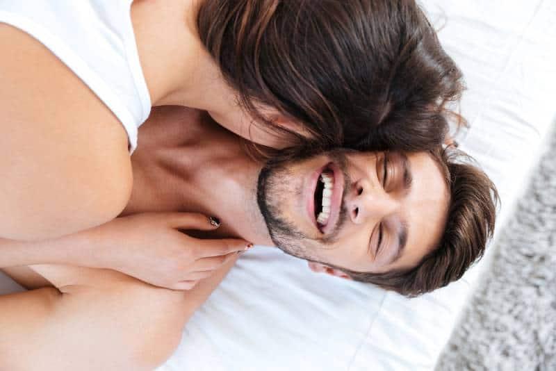 Nahaufnahmeporträt eines jungen lachenden Paares im Bett zu Hause