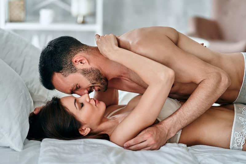 Paar kuschelt auf dem Bett