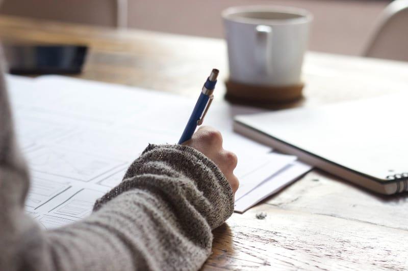 Person, die auf braunem Holztisch nahe weißem Keramikbecher schreibt