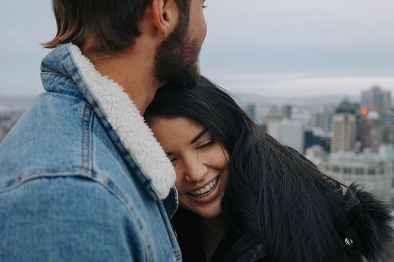 ein lächelndes Mädchen in der Umarmung eines Mannes