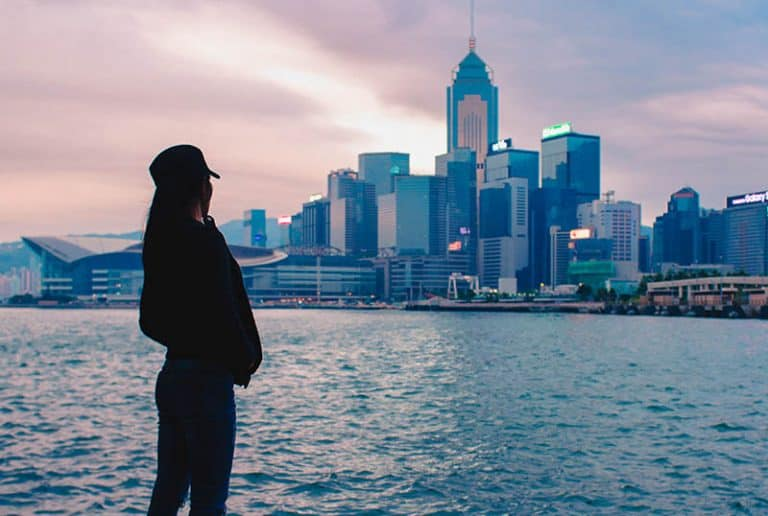 Mädchen mit Hut, das Stadt betrachtet