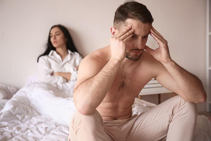 besorgter Mann, der auf der Bettkante sitzt, während Frau auseinander sitzt