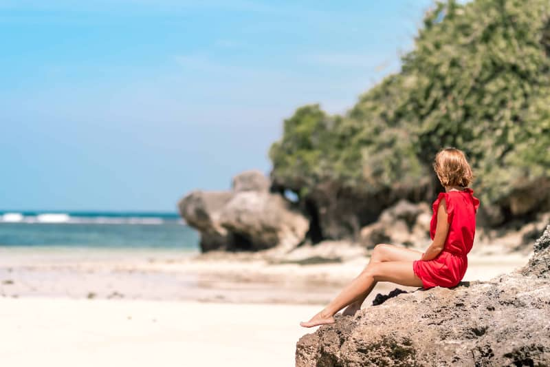 ein Mädchen beobachtet den Strand und sitzt auf einem Felsen(1)