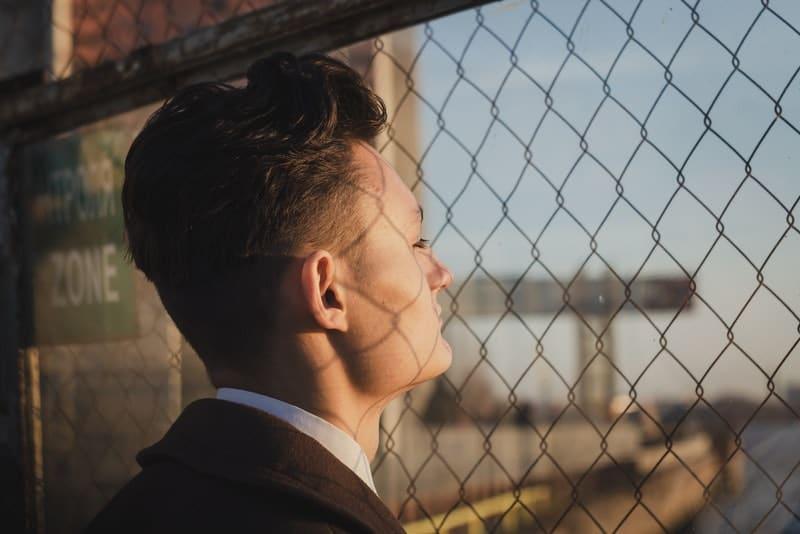 ein Porträt eines Mannes, der eine Landschaft durch einen Zaun betrachtet