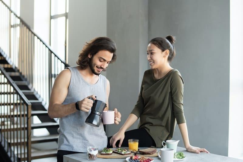 ein lächelndes Liebespaar, das in der Küche frühstückt