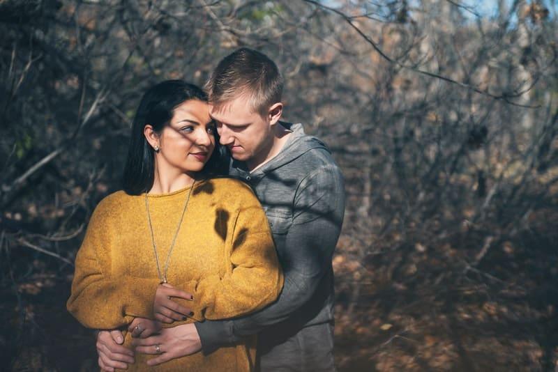 ein liebendes Paar, das in einem Obstgarten umarmt steht