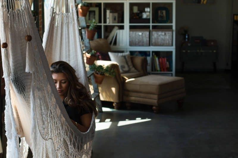 eine Frau, die auf einer Schaukel im Haus liegt