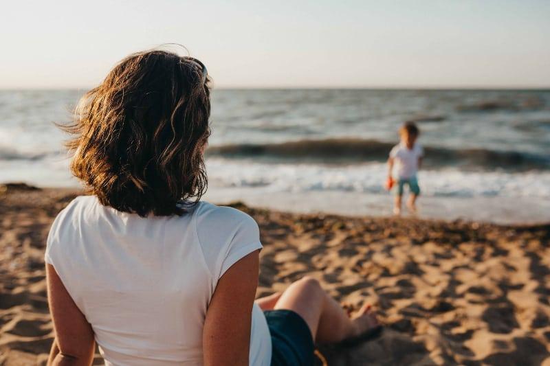 eine Frau, die ein Kind am Strand beobachtet(1)