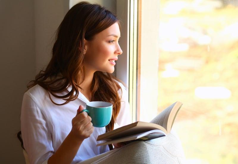 eine junge Frau, die mit einem Buch in der Hand am Fenster sitzt