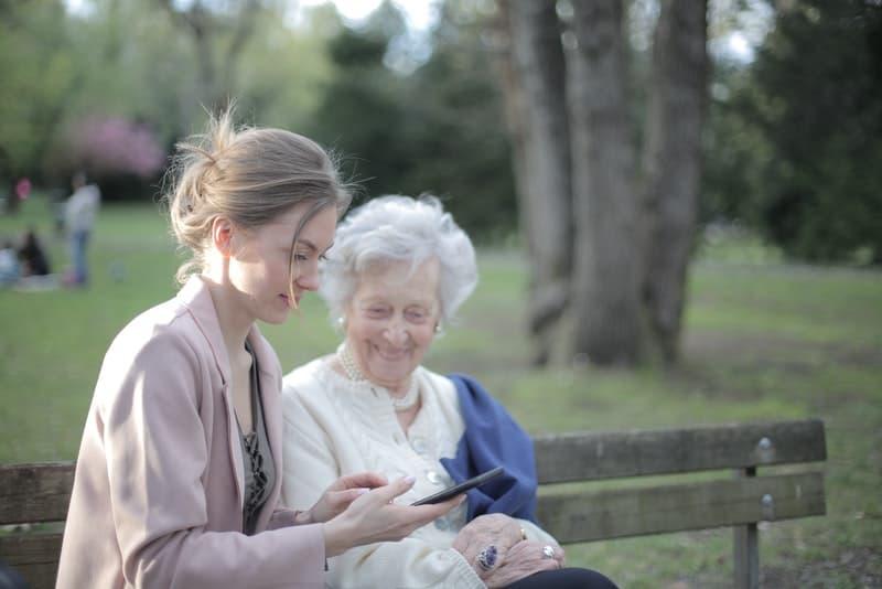 eine lächelnde ältere Frau, die auf einer Bank mit einer Frau sitzt, die eine SMS liest