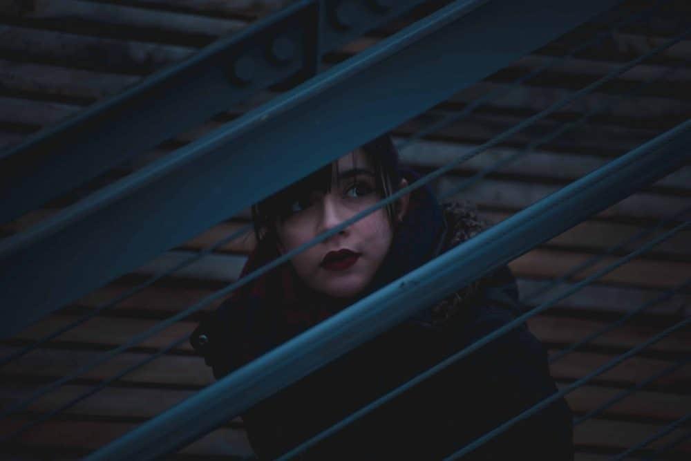 eine traurige nachdenkliche Frau, die auf einer Brücke sitzt