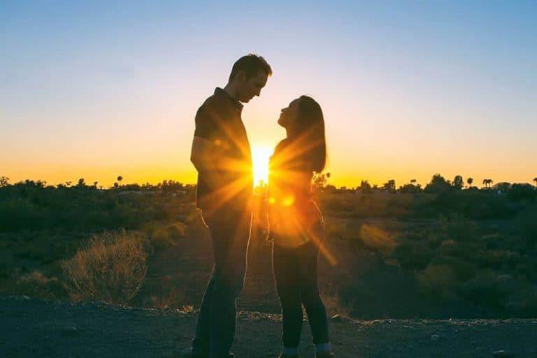 junges Paar sitzt auf dem Gras vor Sonnenuntergang