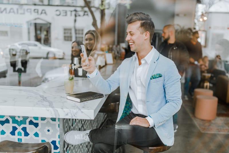 lächelnder Mann beim Halten des Smartphones