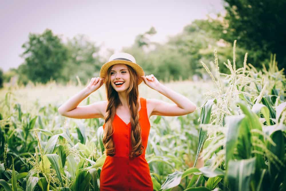 rothaariges glückliches Mädchen in einem roten Kleid mit einem Hut auf dem Kopf, der in einem Maisfeld steht