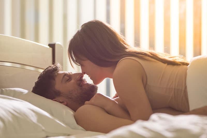 schönes Paar auf dem Bett liegen und einander schauen