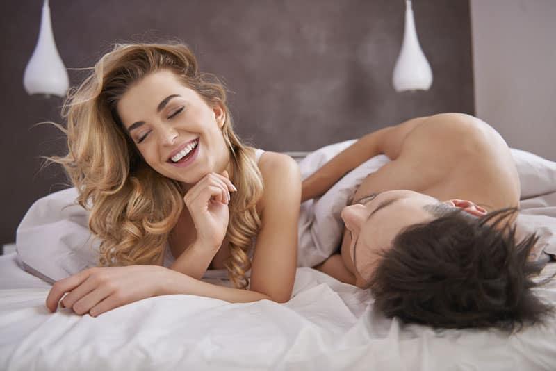 schönes Paar lächelnd im Bett liegend