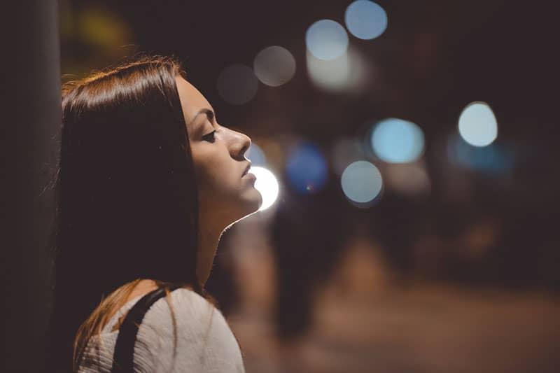 traurige Frau, die nachts allein steht