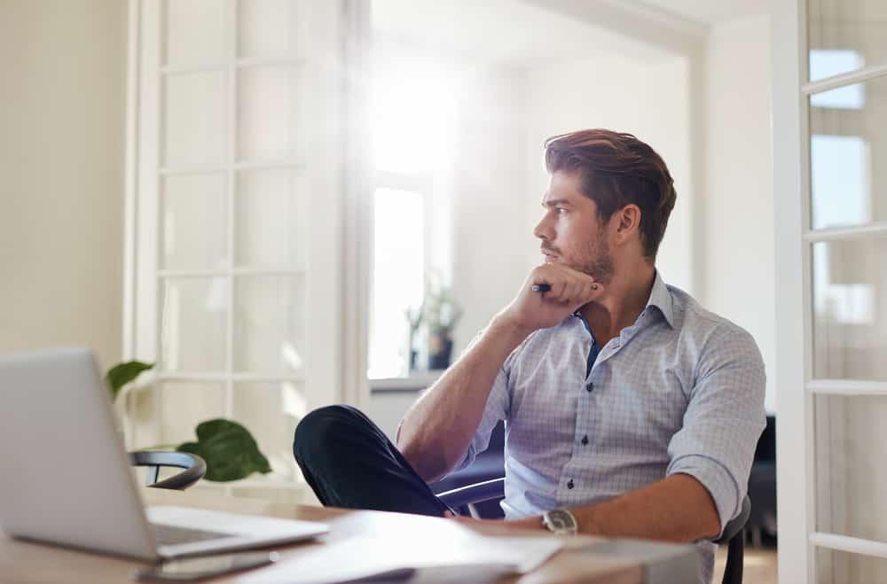 Ein nachdenklicher Geschäftsmann, der in seinem Heimbüro sitzt.